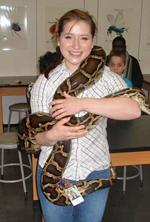 Angela Desjardins tenant un serpent dans ses bras.