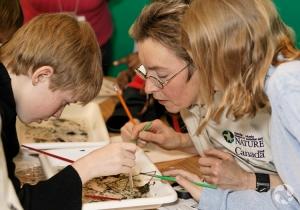 Suzanne Allyson montre des invertébrés aquatiques à des jeunes.