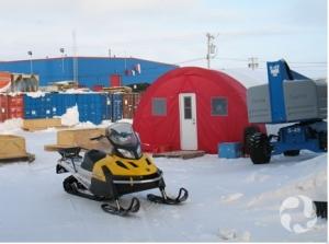 Une motoneige stationnée devant une tente Parcoll en Arctique, avec des conteneurs et un édifice en arrière-plan.