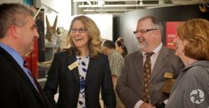 Quatre personnes riant ensemble dans une salle d'exposition.