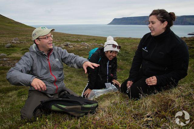 Un homme et deux jeunes filles discutent, agenouillés sur le sol en Islande.