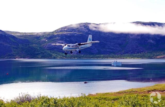Un petit avion au-dessus de l'eau avec des collines et un bateau à l'arrière-plan.