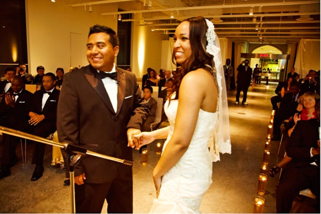 Un couple de mariés souriants durant leur cérémonie de mariage, devant un parterre d'invités.