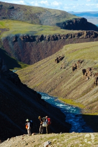Trois personnes au sommet d'un ravin au fond duquel serpente une rivière, sur l'île Victoria en Arctique.