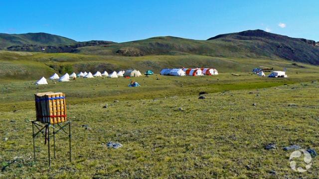Une vingtaine de tentes et de dômes temporaires ainsi qu'un hélicoptère groupés sur une plaine de l'île Victoria, en Arctique.