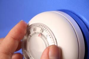 Une main ajustant un thermostat mural.