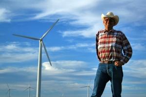 Un homme debout devant des éoliennes.