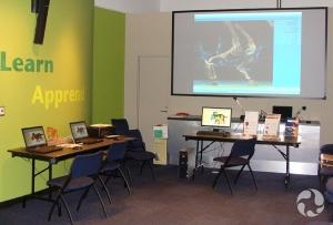 Un espace du Musée comportant trois ordinateurs portatifs disposés sur deux tables et un grand écran.