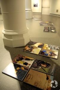 Les photographies de l'exposition sont disposées par terre devant les murs où elles seront accrochées.