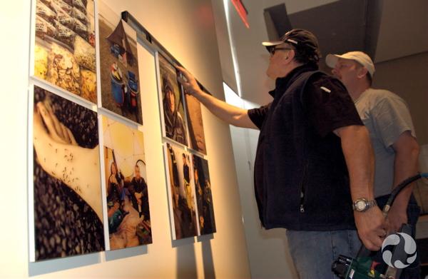 Deux hommes vérifient le niveau et l'espacement des photographies qu'ils ont installées au mur.
