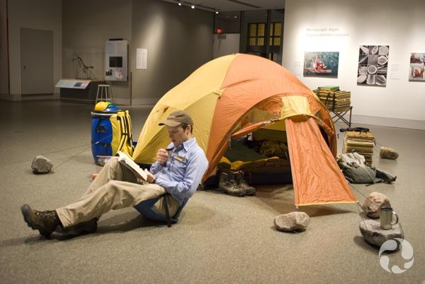 Dans la salle de l'exposition Objectif Arctique, Roger Bull est assis sur une chaise de camp devant une tente, des rochers et des presses pour un herbier.