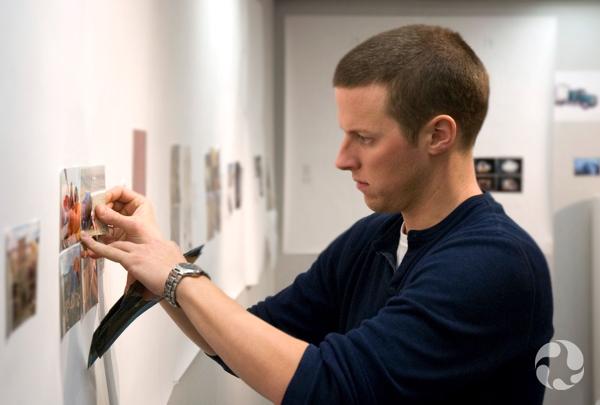 Roger Bull regarde des photographies, debout près d'un mur d'exposition.
