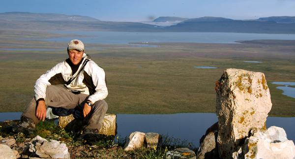 Roger Bull assis sur un rocher, dans la toundra, avec des cours d'eau à l'arrière-plan.