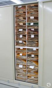 Un classeur vertical, ouvert, laisse voir des étagères remplies de fichiers contenant des plantes séchées.