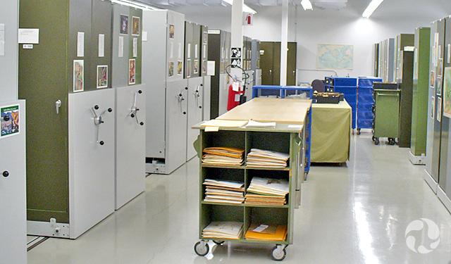 Des rangées de classeurs dans une salle. Au centre, un chariot contenant des fichiers.