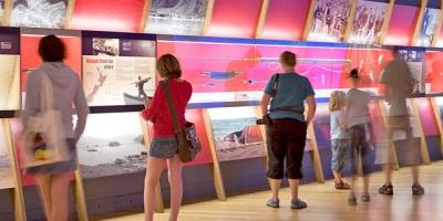 Des visiteurs lisent des panneaux de l'exposition.