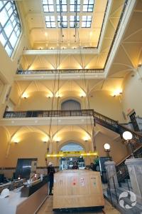 Vue de l'atrium du rez-de-chaussée au quatrième étage avec une caisse sur le point d'être hissée.