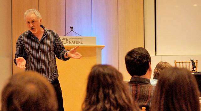 Le professeur Aaron Doyle devant un auditoire dans le Salon du Musée canadien de la nature.
