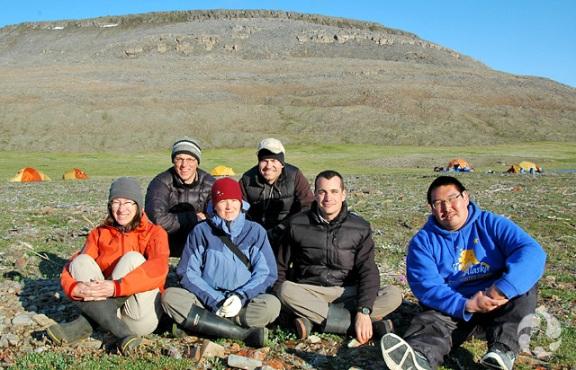 Six personnes dans la toundra. On voit des tentes et des collines à l'arrière-plan.