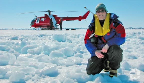 Le chercheur Michel Poulin sur la banquise et hélicoptère en arrière-plan.