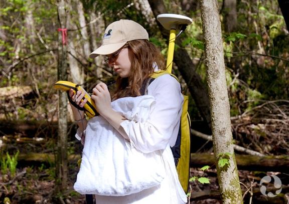 Cassandra Robillard effectue un relevé avec un lecteur GPS sur les terrains du Musée.