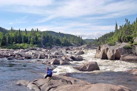 Un homme assis sur un rocher en bordure de la rivière Romaine, au Québec.