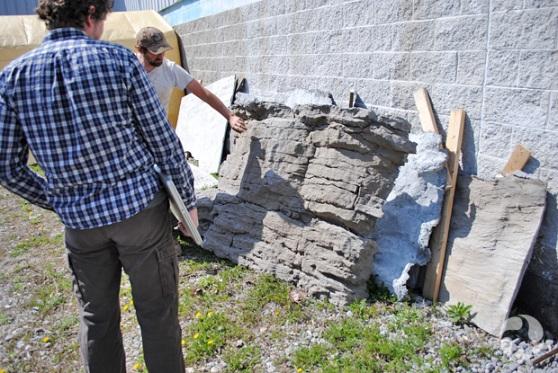 Deux hommes examinent des échantillons de roches, pour recouvrir le mur de la future grotte.