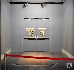 Deux portes d'acier closes au bout d'un large passage.