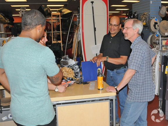 Deux commis et deux clients discutent dans un magasin d'équipement de sport.
