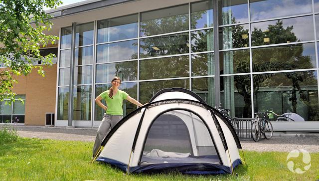 Une jeune fille debout près d'une tente, devant l'édifice qui abrite les collections et les activités de recherche du Musée.