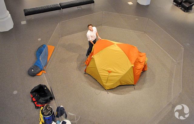 Vue en plongée dans une galerie du Musée où un homme démonte une tente.