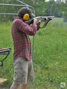 Un homme tirant à la carabine dans un champ de tir extérieur.