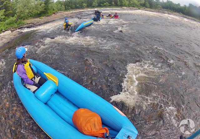 Une femme dans une embarcation gonflable regarde un groupe de personnes debout dans la rivière, qui tentent de monter à bord d'une autre embarcation.