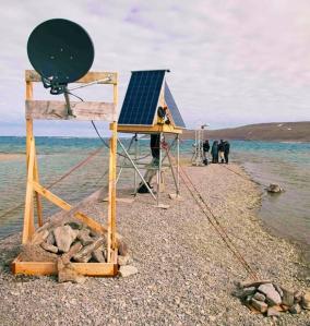 Trois petites tours portant une antenne parabolique, des panneaux solaires et une caméra sont alignées sur une pointe de gravier.
