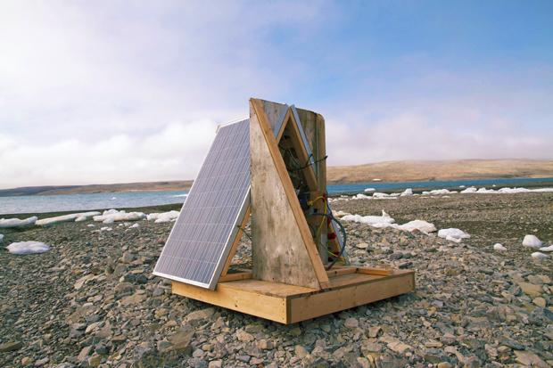 Panneaux solaires appuyés contre une plate-forme en bois sur une plage rocailleuse.