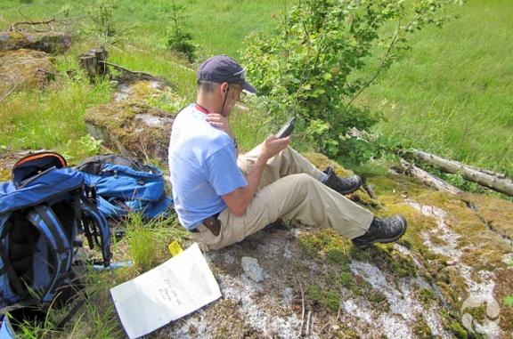 Un homme assis par terre consulte un appareil de GPS dans sa main.