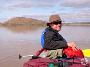 Un homme assis dans un canot sur l'eau, avec une colline en arrière-plan.
