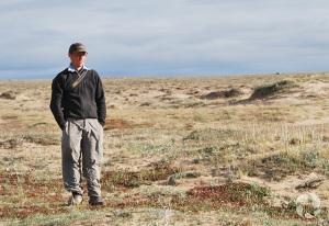 Un homme debout parmi des dunes de sable.