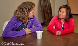 Deux femmes assises à une table en train de parler.