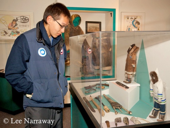 Un jeune homme regarde des artéfacts dans une vitrine.
