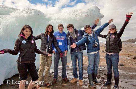 Six adolescents, les bras tendus, devant un énorme morceau de glace.