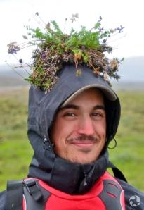 Un homme porte une plante sur sa tête, avec racines et motte de terre.