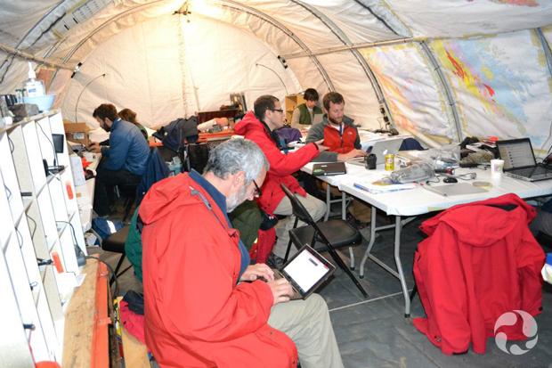 Un homme avec son ordinateur sur les genoux au premier plan, et d'autres assis à des tables dans une grande tente.