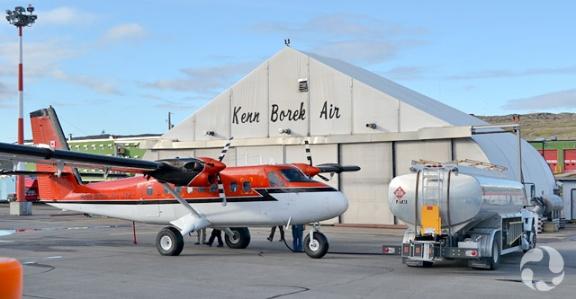 Petit avion rouge devant un hangar.