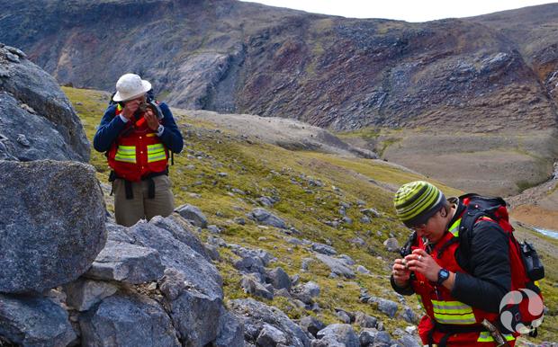 Deux personnes sur un terrain en pente en train d'examiner des roches qu'ils tiennent dans leur main.