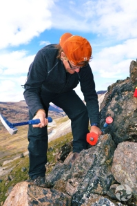 Une femme lève son marteau en regardant une surface rocheuse.