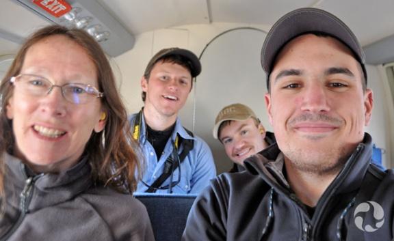 Quatre personnes assises dans la cabine d'un petit avion.