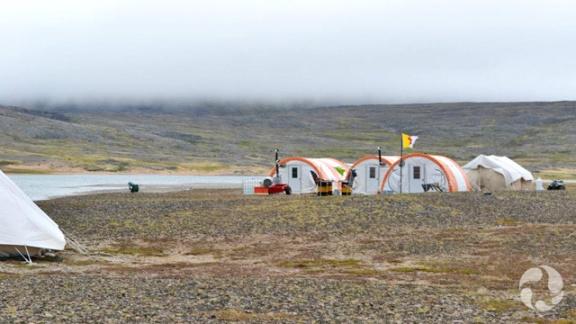 Quatre abris en forme de demi-dôme sur un terrain plat.