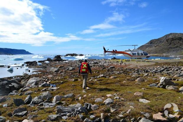 Un homme se dirigeant vers un hélicoptère posé sur un terrain herbeux près de l'eau.