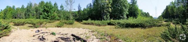 Vue d'une prairie avec terrain sablonneux au premier plan.